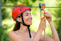 Woman riding on a zip line. Young and smiling woman in red helmet preparing to ride on a zip line in the forest. Close up view focused on hands and face stock photos