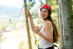 Woman riding on a zip line. Young and smiling woman in red helmet preparing to ride on a zip line in the forest. Close up view focused on hands and face royalty free stock image