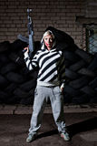 Woman with a riffle. Dangerous young woman holding automatic rifle in front of old tires Royalty Free Stock Photos