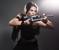 Woman with rifle. On dark royalty free stock images