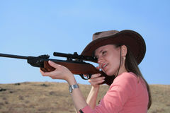 The Woman with rifle. The young  woman with rifle is shooting Stock Photo