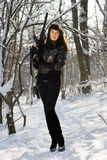 Woman with a rifle in winter forest Stock Photo