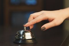 Woman ringing hotel reception service bell closeup. Woman ringing hotel service bell to attract attention in modern hotel, dark background, copy space Stock Photography