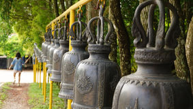 Woman ringing a row of temple bells in thailand Stock Photography