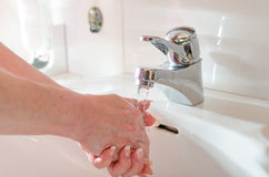 Woman rinsing her hands. In sink with water Royalty Free Stock Photography