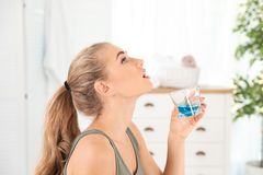 Woman rinsing mouth with mouthwash. In bathroom. Teeth care royalty free stock photography