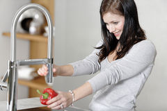 Woman rinsing peppers in a sink Royalty Free Stock Photos