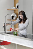 Woman rinsing peppers in a sink Stock Photography
