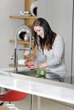 Woman rinsing peppers in a sink Stock Images