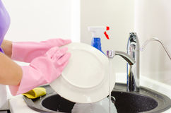 Woman rinsing plates under the tap Royalty Free Stock Photography