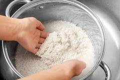 Woman rinsing rice. In saucepan Royalty Free Stock Photo