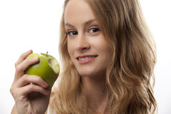 Woman with ripe green apple. Attractive young blond haired woman with ripe green apple with bite mark; isolated on white background royalty free stock photo