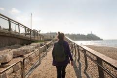 Female tourist walks along the embankment towards the city stock photos
