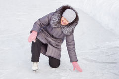 Woman is rising after the fall at a rink Royalty Free Stock Images