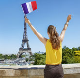 Woman rising French flag in front of Eiffel tower in Paris Royalty Free Stock Images