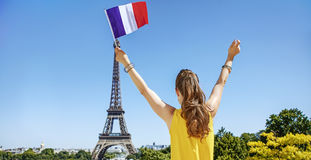 Woman rising French flag in front of Eiffel tower in Paris Stock Photos