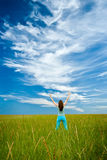 Woman rising up hands. On green field royalty free stock photography