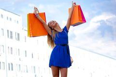 Woman rising up shopping bags Royalty Free Stock Images