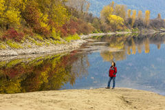 Woman by river in autumn. Royalty Free Stock Images