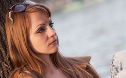Woman on river. A beautiful young woman sitting on the bank of the river and thinking about something Stock Images