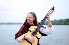 Woman on the river playing celtic medieval music,Ukraine. KIEV,UKRAINE - MAY 31:Unidentified beautiful woman on the river playing celtic medieval music in Stock Photography