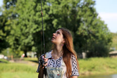 Young woman with summer sprouts and dungarees while fishing Stock Image