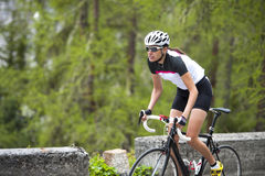 Woman road cycling uphill. A woman by raod cycling uphill Royalty Free Stock Photo