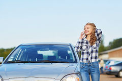 Woman on the road near a broken car calling for help Royalty Free Stock Photo