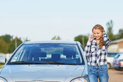 Woman on the road near a broken car calling for help Stock Photography