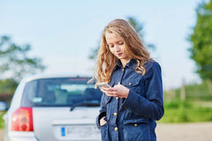 Woman on the road near a broken car calling for help Royalty Free Stock Photography