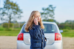 Woman on the road near a broken car calling for help Stock Photo