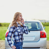 Woman on the road near a broken car calling for help Stock Images