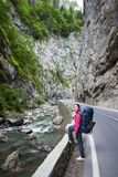 Woman on road next to mountain stream in Bicaz Gorge. Pretty woman with backpack on road next to a mountain stream in the Bicaz Gorge. Canyon is one of the most Stock Image