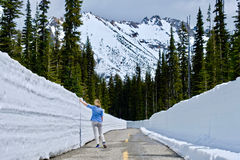 Woman on the road with snow walls. North Cascades National Park. Bellingham. Seattle. Cascade mountains. Washington. The United States Royalty Free Stock Photography