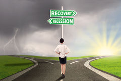 Woman on the road to recovery or recession finance. Female worker standing on the road and look at the signpost pointing on the road to recovery or recession Royalty Free Stock Photo