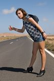 Woman on the road waiting for a car Stock Photography