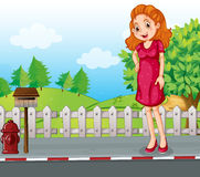 A woman at the roadside near the wooden mailbox Stock Photos