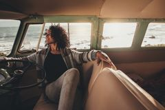 Woman on roadtrip relaxing in the van. African woman sitting in a van and relaxing, Young female on road trip travelling by a mini van Royalty Free Stock Photo