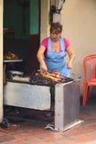 Woman Roasting Guinea Pig in Banos, Ecuador Stock Photography