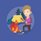 Woman roasting marshmallow over campfire. Royalty Free Stock Photography