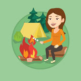 Woman roasting marshmallow over campfire. Stock Photo