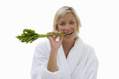 Woman in robe eating celery stick, cut out.  royalty free stock image