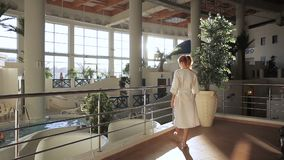 Woman in a robe looks over magnificent pool complex inside big hall. Female visitor of complex`s spa watches luxurious indoor space where people rest in water stock footage