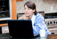 Woman in robe using laptop computer over coffee. An attractive woman in robe using a laptop computer while drinking a cup of coffee Stock Image