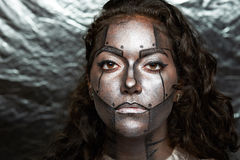 Woman with robot face. Body art on silver background stock images