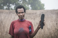 Woman with a rock. Baliem Valley, West Papua, Indonesia, February 14th, 2016: a woman showing off a rock she uses to take care of her land royalty free stock photo