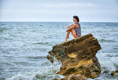 Woman on rock in beach Royalty Free Stock Image