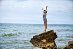 Woman on rock in beach Stock Images