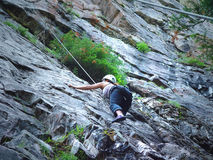 Woman rock climber in the Canadian Rockies. Female rock climber meets the challenge on a rock crag at Lake Louise, Banff National Park, Canada stock photography