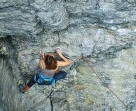 Woman rock climber on the cliff Stock Photos